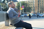 Stock Video Footage of Man sitting on street bench and eating croissant.