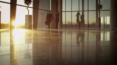 Stock Video Footage of Diverse business group walking through modern office building at sunset