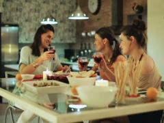 Women partying using tablet talking and drinking wine. Stock Footage