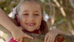 Little Girl Pulls Herself Up Onto Tree Branch And Smiles With Pride Stock Footage