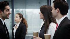Attractive diverse business group chatting together in large modern office build - stock footage