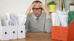 Sad, overwhelmed by too much paperwork businessman in the office HD Stock Footage