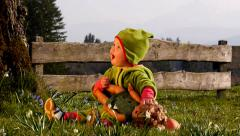 Girl sitting in the garden and playing with a doll - stock footage