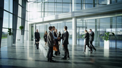Business people meet and shake hands in large modern office building Stock Footage