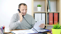 Businessman with documents talking on telephone in the office HD Stock Footage