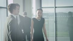 Business people chatting as they walk through large modern office building - stock footage