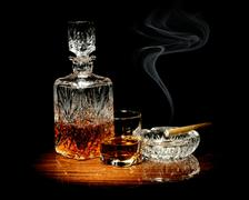 whisky in a carafe and glass and a cigar in ashtray isolated on black - stock photo