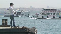 A local Turkish man fishing in front of an Istanbul scenery (Editorial) - stock footage