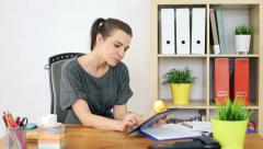 Young businesswoman eating apple, surfing net on tablet in the office HD Stock Footage