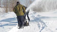 Men shoveling snow machine and shovel Stock Footage
