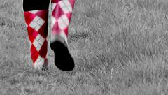 Red and white boot steps in the grass - stock footage