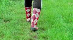 Red and white boot steps in the grass Stock Footage