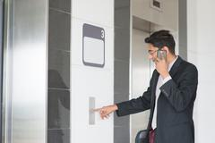 indian businessman entering elevator - stock photo