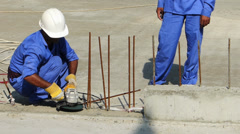 Dubai Marina construction site foreign workers cutting metal pole in hot sun UAE Stock Footage