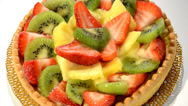 Stock Video Footage of A dessert. Fruit tart on white plate rotating.
