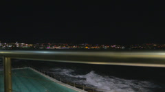 A cinematic dolly shot overlooking bondi iceberg and beach in evening Stock Footage