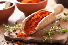 Red ground paprika spice in wooden scoop and bowl Stock Photos