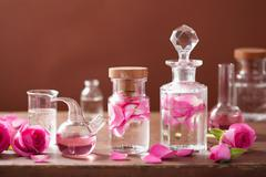 Alchemy and aromatherapy set with rose flowers and flasks Stock Photos