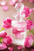 perfume bottle and pink rose flowers. spa aromatherapy - stock photo