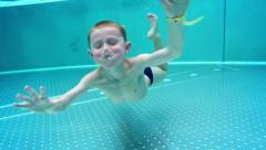Playfull boy dives in hot winter pool Stock Footage