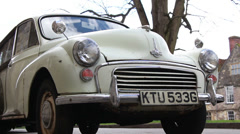 Classic Morris Minor with English city background Stock Footage