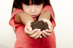 girl holding soil - stock photo