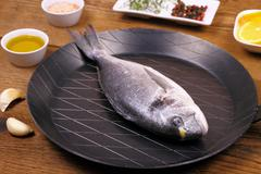 Fresh bream fish on frying pan and ingredients Stock Photos