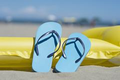 Pair of light blue flip-flops leaning on yellow airbed on the beach - stock photo