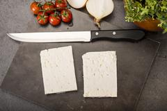 Preparation of low carb dish baked Feta cheese - stock photo