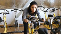 Female exercising their legs doing cardio cycling training - stock footage