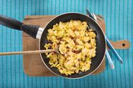 Stock Photo of Scrambled eggs with ham cubes in frying pan