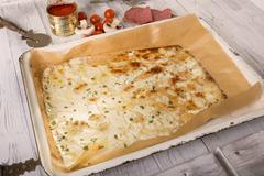 Baking tray of low carb pizza base on wooden table with mozzarella, cream cheese - stock photo