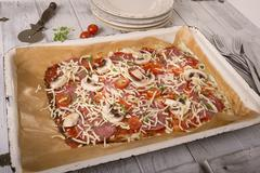 Baking tray of unbaked low carb pizza on wooden table - stock photo