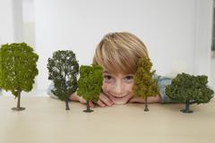 Boy sitting at table with tree models, environmental conservation - stock photo