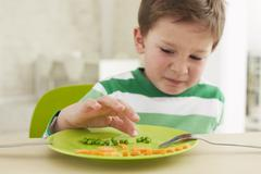 Boy eating peas and carrots showing anthropomorphic face - stock photo