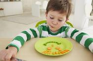 Stock Photo of Boy eating peas and carrots showing anthropomorphic face
