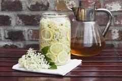 White elderflowers and lemon in glass bowl, edible flowers, European Black Elder - stock photo