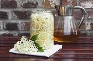 Stock Photo of White elderflowers and lemon in glass bowl, edible flowers, European Black Elder