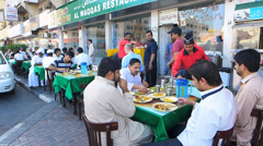 Dubai Pakistani foreign migrant worker eating at outdoor Pakistan restaurant UAE Stock Footage