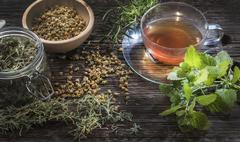 Tea cup of peppermint, rosmary and  chamomile blossoms and fresh mint (Mentha), Stock Photos