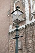 Germany, North Rhine-Westphalia, Aachen, historic street lamp in front of brick Stock Photos