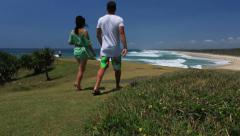 Couple walking along beach headland - stock footage
