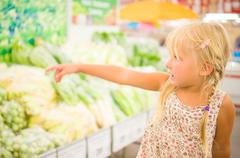 Adorable girl near shelf with vegetables at supermarket Stock Photos