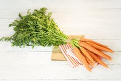 Bunch of organic carrots on cloth and white wooden table - stock photo