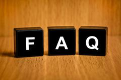 faq or frequently asked questions text on block - stock photo