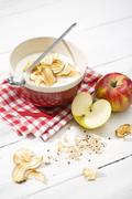 Bowl of lactose-free yogurt with dried apple rings and and apples on white Stock Photos
