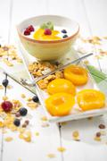 Bowl of lactose-free yogurt with pieces of peach, raspberries, blueberries and Stock Photos
