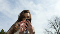 Woman holding Cell Phone in park. Stock Footage