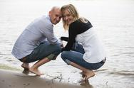 Stock Photo of Germany, Rhineland-Palatinate, young couple crouching at waterside of Rhine