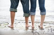 Stock Photo of Naked feet of young couple standing in the water of Rhine river